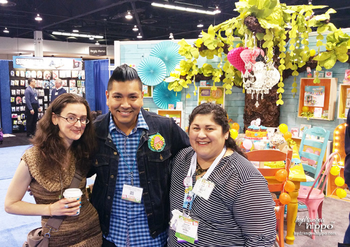 Rhonda Greene, Richard Garay, and Jennifer Priest in front of the Spellbinders booth at CHA 2015.