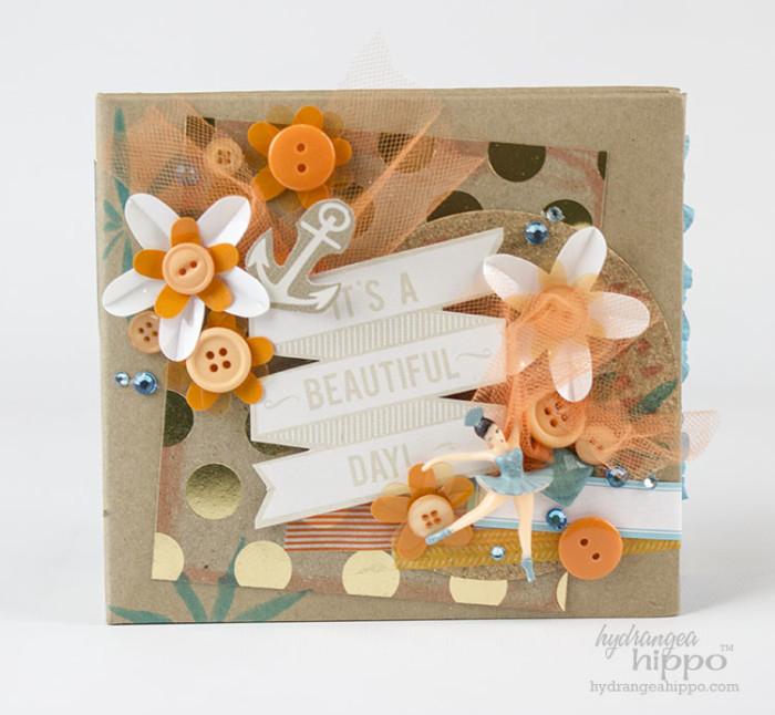 Decorate a mini album cover with bulky embellishments to make it fun.